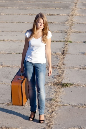 beautiful girl with a suitcase outdoors shooting
