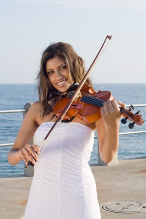 young indian woman play violin on beach